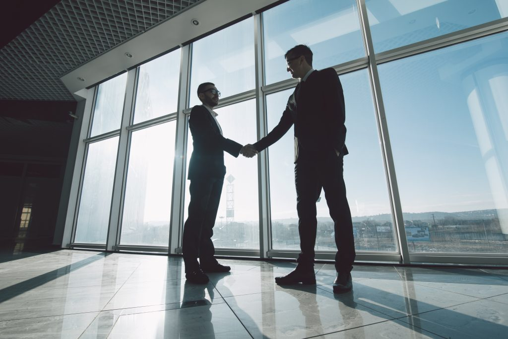 Two,Young,Businessmen,Are,Shaking,Hands,With,Each,Other,Standing